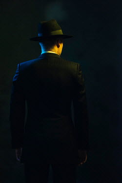 Ysbrand Cosijn Gangster with pinstripe suit and fedora in shadow from behind