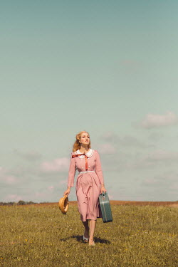 Joanna Czogala Young woman in vintage pink dress walking in field with straw hat and suitcase