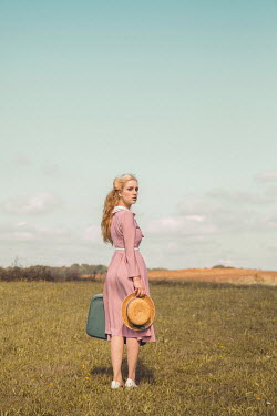 Joanna Czogala Young woman in vintage pink dress holding straw hat and suitcase in field
