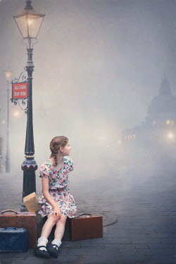 Lee Avison evacuee girl at dawn waiting under a streetlight with luggage
