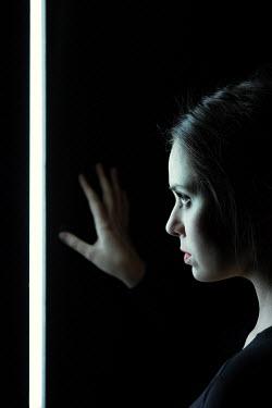 Magdalena Russocka woman looking through chink in wall