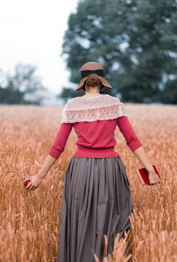 Mary Wethey Victorian woman in  straw hat walking in wheat field