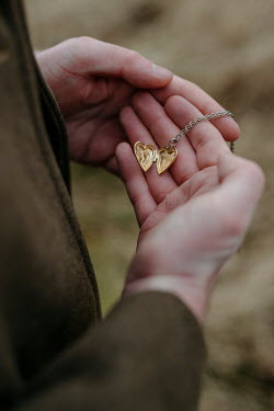 Shelley Richmond Hands of man holding gold locket