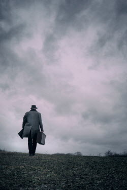 Tim Robinson MAN CARRYING SUITCASE IN COUNTRYSIDE AT DUSK Men