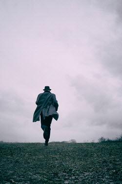 Tim Robinson MAN IN HAT RUNNING IN WINTRY FIELD Men