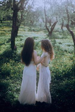 Irina Orwald TWO WOMEN STANDING IN SUMMERY ORCHARD Women