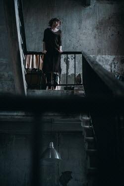 Irina Orwald WOMAN STANDING ON LANDING IN SHABBY HOUSE Women
