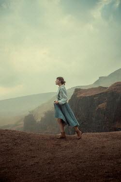 Rekha Garton WOMAN WALKING ON CLIFF EDGE IN MOORLAND Women