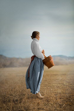 Ildiko Neer Historical woman standing in field with basket
