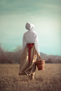 Ildiko Neer Historical servant standing in field with basket