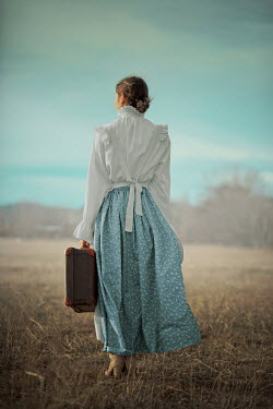 Ildiko Neer Historical servant standing in field with suitcase