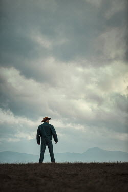 Magdalena Russocka cowboy standing in field with mountains