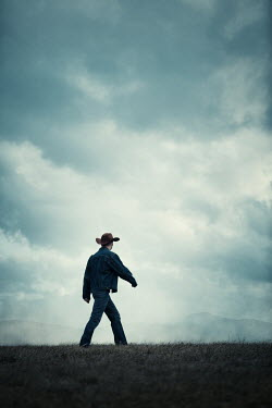 Magdalena Russocka cowboy walking in field with mountains
