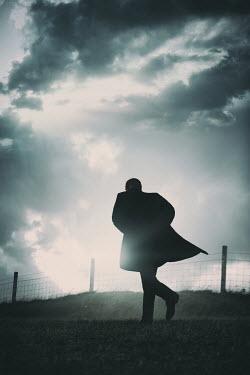 Magdalena Russocka modern man running along mesh fence