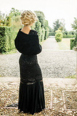 Nikaa Young woman with black fur shawl and dress in garden