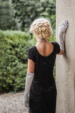 Nikaa Young woman wearing vintage black dress in garden