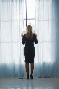 Ildiko Neer Modern woman standing by window