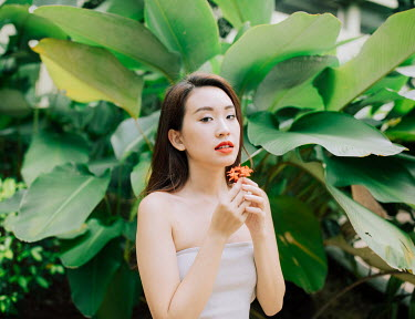 Jessica Lia Young woman with orange flower by tropical tree