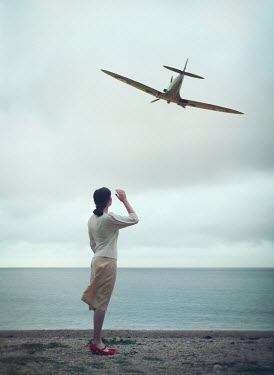 Mark Owen Woman in vintage sweater watching WWII fighter plane flying over beach