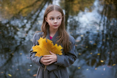 Alexander Vinogradov Girl in grey coat holding yellow autumn leaf