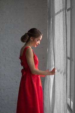 Ildiko Neer Woman in evening gown standing at window