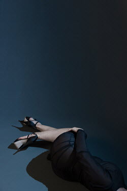 Paolo Martinez Legs of woman in black dress and high heels lying in shadow