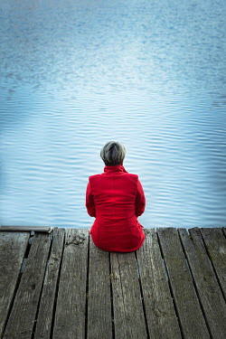 Paolo Martinez Woman in red coat sitting on wharf