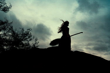 Rekha Garton Silhouette of witch with broomstick on hill