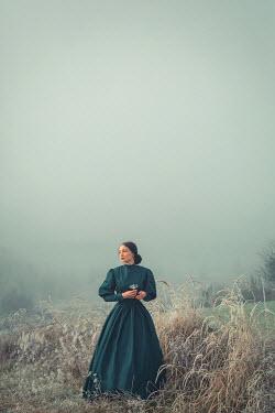 Joanna Czogala HISTORICAL WOMAN STANDING IN MISTY COUNTRYSIDE Women