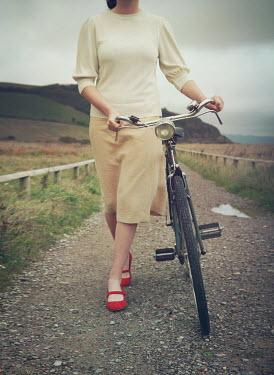 Mark Owen WOMAN WITH BICYCLE ON COASTAL PATH Women