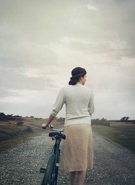 Mark Owen WOMAN PUSHING BICYCLE ON COUNTRY LANE Women