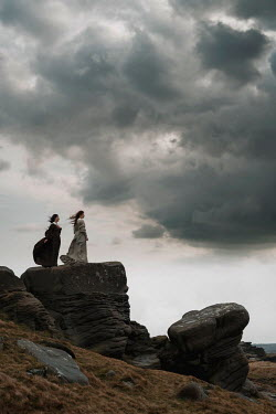 Rekha Garton TWO HISTORICAL WOMEN ON ROCKS IN WINDY COUNTRYSIDE Women