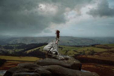 Rekha Garton HISTORICAL WOMAN ON ROCKS IN STORMY COUNTRYSIDE Women