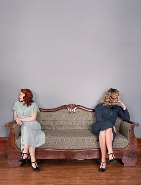 Elisabeth Ansley TWO RETRO WOMEN SITTING APART ON SOFA Women