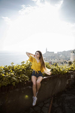 Greta Larosa HAPPY GIRL SITTING ON WALL WITH TOWN AND OCEAN Women