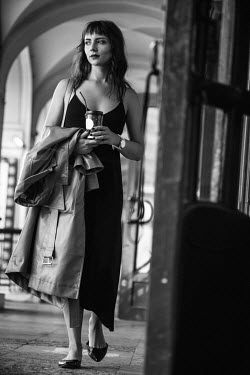 Maria Yakimova WOMAN CARRYING COAT AND DRINK IN CITY Women
