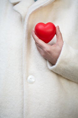 Alison Archinuk WOMAN IN WHITE COAT HOLDING RED HEART Women