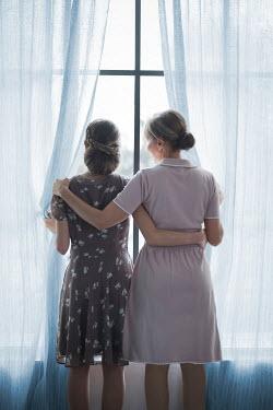 Ildiko Neer TWO WOMEN HUGGING INDOORS BY WINDOW Women