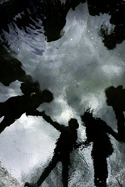 Ute Klaphake SILHOUETTES OF CHILDREN HOLDING HANDS REFLECTED IN PUDDLE Groups/Crowds