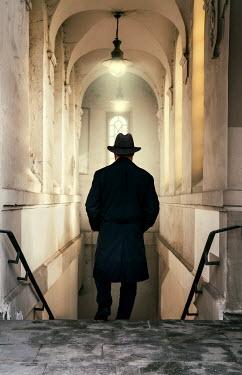 Jaroslaw Blaminsky RETRO MAN IN HAT DESCENDING STEPS IN OLD BUILDING Men