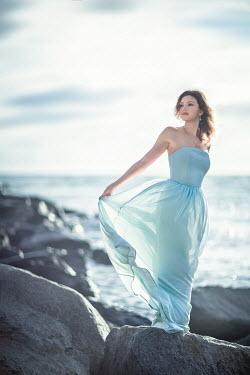 Evelina Kremsdorf WOMAN IN SILK DRESS ON ROCKS BY SEA Women