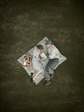Mary Wethey COUPLE LYING ON RUG WITH PICNIC FROM ABOVE Couples