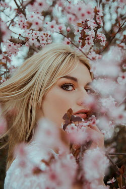 Greta Larosa Young woman under cherry blossom tree
