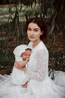 Nathalie Seiferth Young woman in wedding dress holding baby