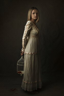 Robin Macmillan Woman in white dress holding birdcage behind her back