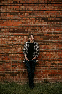 Rachel Nichole Teenage boy in plaid shirt leaning on brick wall Men