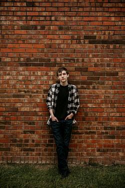 Rachel Nichole Teenage boy in plaid shirt leaning on brick wall