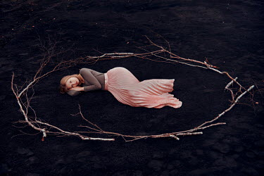Nathalie Seiferth Young woman lying in circle of sticks