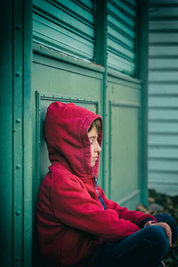 Galya Ivanova BOY IN RED HOODIE SITTING DAYDREAMING Children