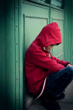 Galya Ivanova SAD BOY IN RED HOODIE CROUCHING BY DOORS Children